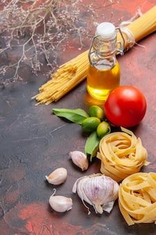 Vooraanzicht ruwe deegwaren met olie en tomatoe op de donkere deegwaren van het oppervlak