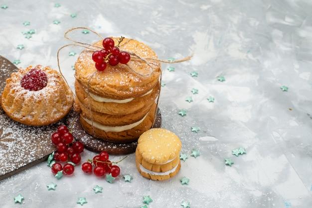 Vooraanzicht sandwichkoekjes gebonden met crèmevulling samen met cake op het donkere bureau
