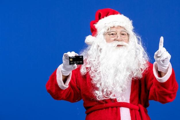 Vooraanzicht santa claus in rood pak met bankkaart op blauw aanwezig xmas kleur nieuwjaar vakantie