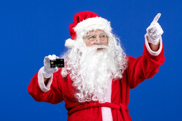 Vooraanzicht santa claus in rood pak met bankkaart op blauw aanwezig xmas kleur nieuwjaarsvakantie