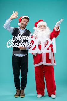 Vooraanzicht santa claus met jonge mannelijke bedrijf vrolijk kerstfeest en geschriften op de blauwe achtergrond