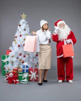 Vooraanzicht santa claus met jonge vrouw rond kerstboom en cadeautjes op grijs bureau