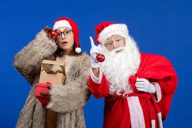 Vooraanzicht santa claus met jonge vrouwelijke handtas met cadeautjes en speelgoed op de blauwe vakantie xmas kleur nieuwjaar
