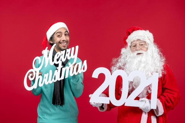 Vooraanzicht santa claus met mannelijke holding en merry christmas geschriften op rode nieuwjaar kerstcadeautjes emotie vakantie