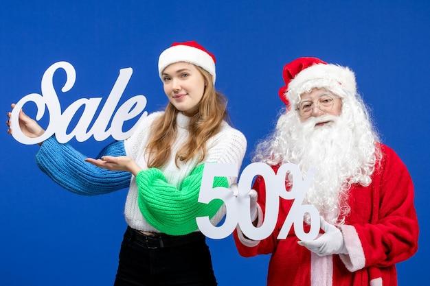 Vooraanzicht santa claus met vrouwelijke verkoopgeschriften op blauwe vakantie koude kerst nieuwjaar sneeuw winkelen