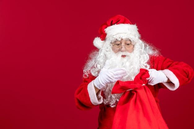 Vooraanzicht santa claus opening zak vol cadeautjes voor kinderen op rode feestdagen kerstemotie