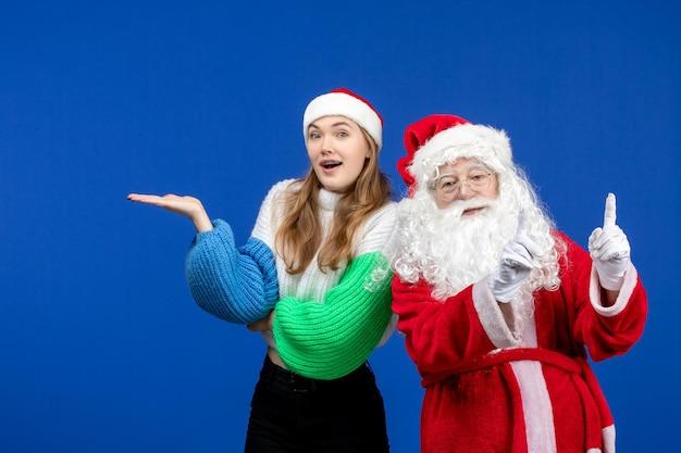 Vooraanzicht santa claus samen met jonge vrouw staande op blauwe nieuwjaarsvakantie kerst emotie kleur