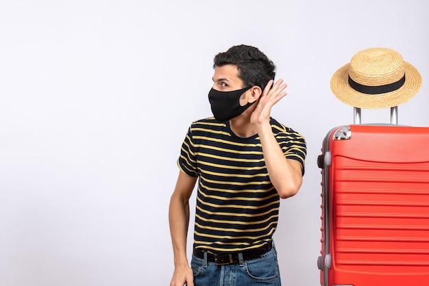 Vooraanzicht sceptische jonge toerist met zwart masker dat zich dichtbij rode koffer bevindt die iets luistert
