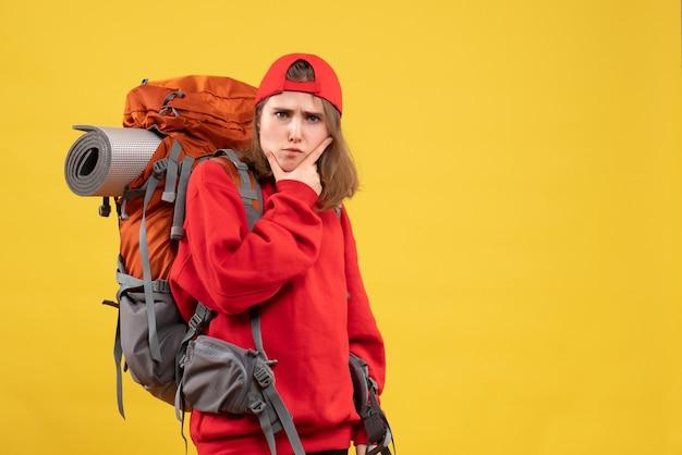 Vooraanzicht sceptische vrouwelijke reiziger met rugzak hand op haar kin te zetten