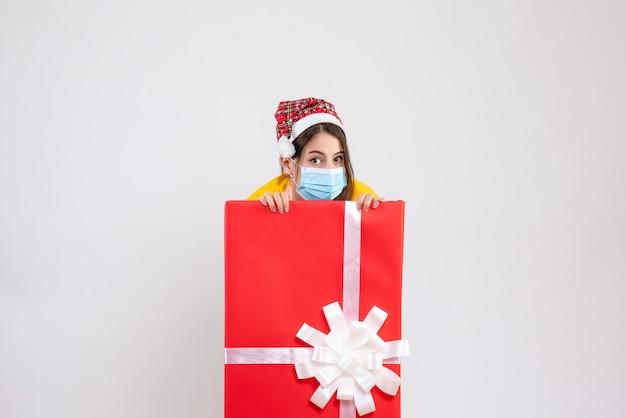 Vooraanzicht schattig kerst meisje met kerstmuts verstopt achter grote kerst cadeau