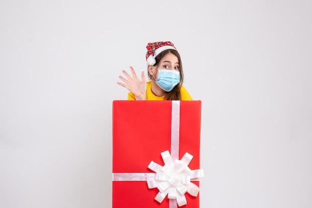 Vooraanzicht schattig meisje met kerstmuts begroetende staande achter grote kerstcadeau