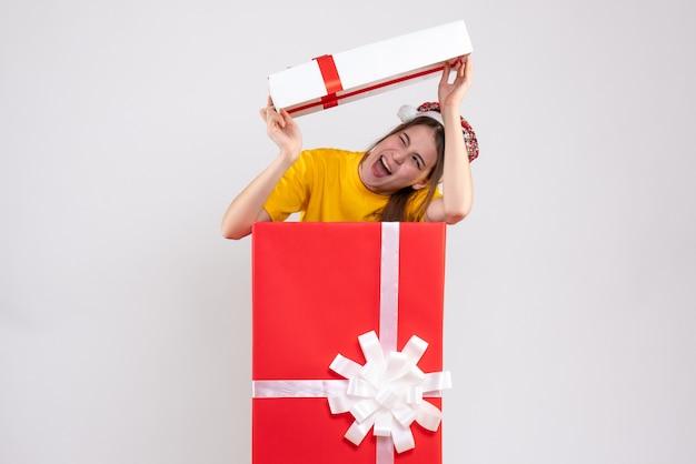 Vooraanzicht schattig meisje met kerstmuts doos deksel opheffen boven haar hoofd staande achter grote kerstcadeau