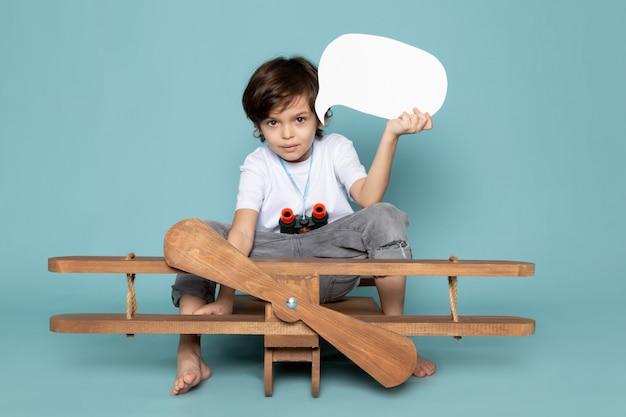 Vooraanzicht schattige jongen in wit t-shirt en grijze spijkerbroek op de blauwe vloer