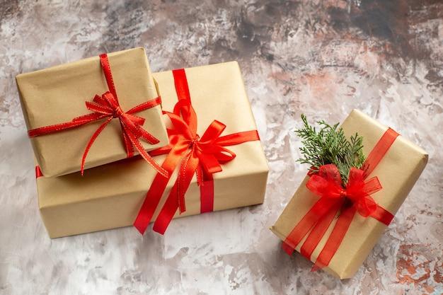 Vooraanzicht schattige kerstcadeautjes vastgebonden met rode strikken op de lichte achtergrond