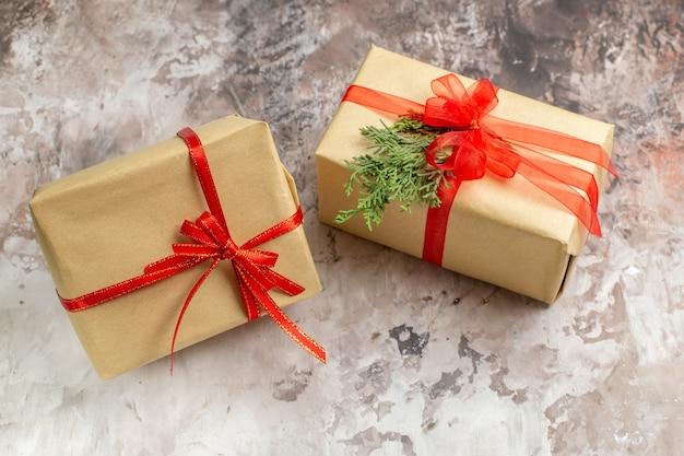 Vooraanzicht schattige kerstcadeautjes vastgebonden met rode strikken op licht bureau