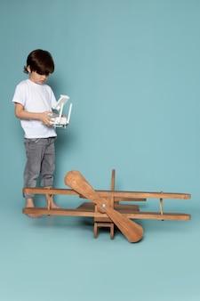 Vooraanzicht schattige schattige jongen controlerende houten vliegtuig op het blauwe bureau
