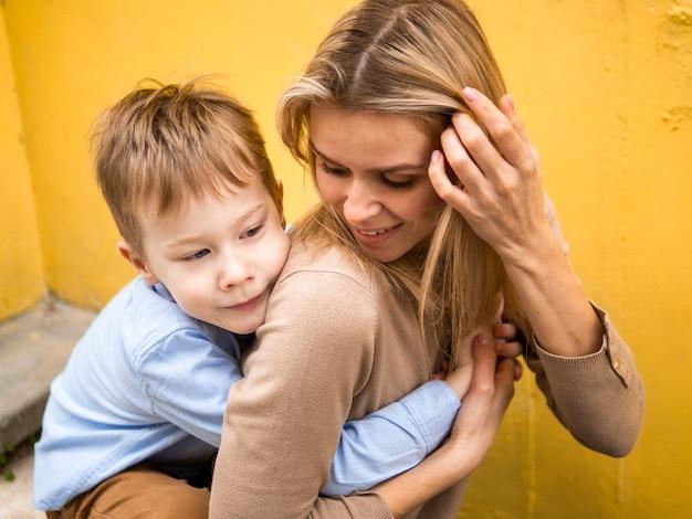 Vooraanzicht schattige zoon knuffelen zijn moeder