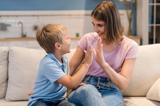 Vooraanzicht schattige zoon spelen met moeder
