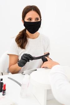 Vooraanzicht schoonheid nagel werknemer gezichtsmasker en handschoenen dragen