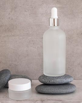 Vooraanzicht schoonheidsproducten in ontvangers op grijze rotsen