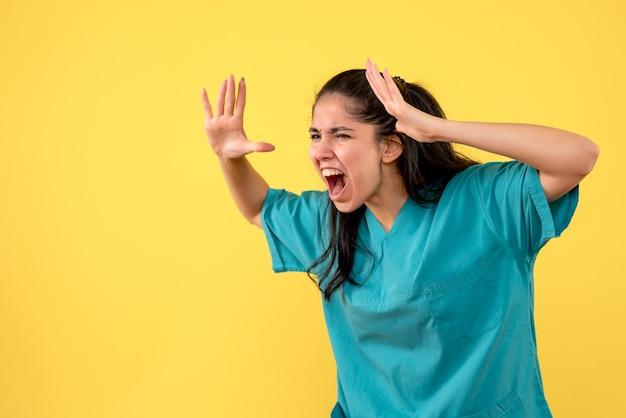 Vooraanzicht schreeuwende vrouwelijke arts die zich op gele achtergrond bevindt