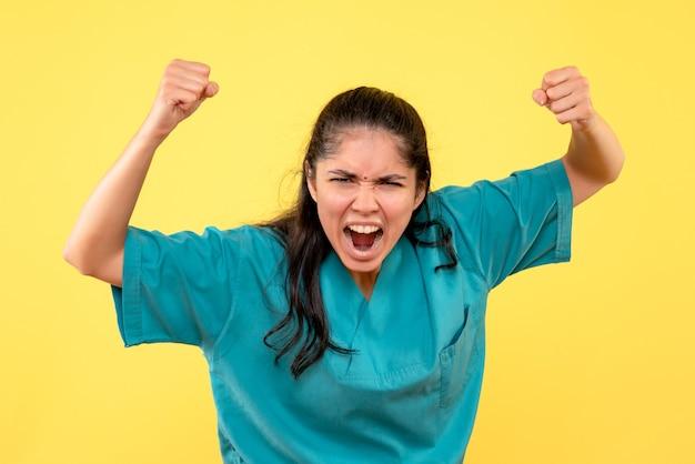Vooraanzicht schreeuwende vrouwelijke arts in uniform staande op gele geïsoleerde achtergrond
