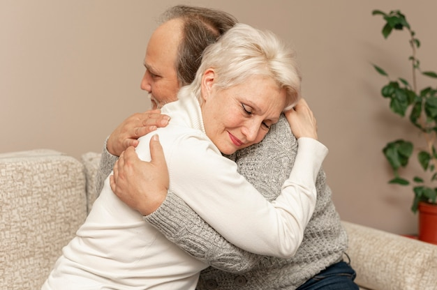 Vooraanzicht senior koppel op bank knuffelen