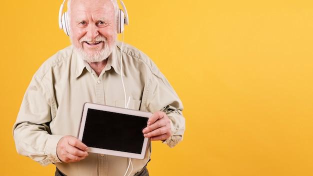 Vooraanzicht senior met tablet luisteren muziek