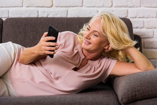 Vooraanzicht senior vrouw op zoek op haar telefoon