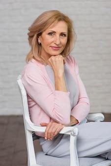 Vooraanzicht senior vrouw zittend op een stoel