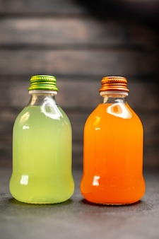 Vooraanzicht sinaasappel en geel sap op donkere achtergrond