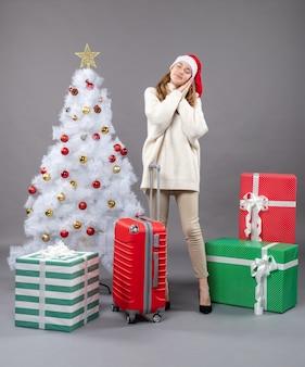Vooraanzicht slaperig xmas meisje met kerstmuts staande in de buurt van witte kerstboom