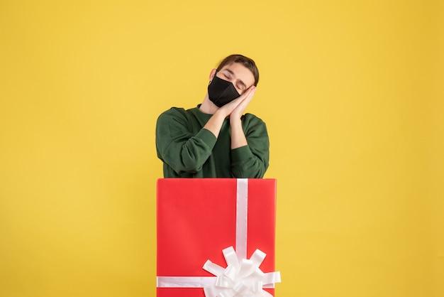 Vooraanzicht slaperige jonge man achter grote geschenkdoos op gele achtergrond