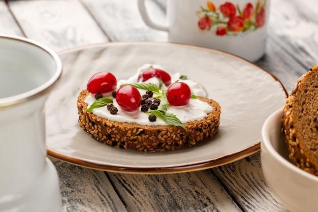 Vooraanzicht sluit brood toast met zure room en kornoeljes op grijs