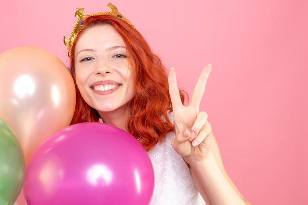 Vooraanzicht sluit jong wijfje dat kleurrijke ballons houdt en naar de camera op roze glimlacht