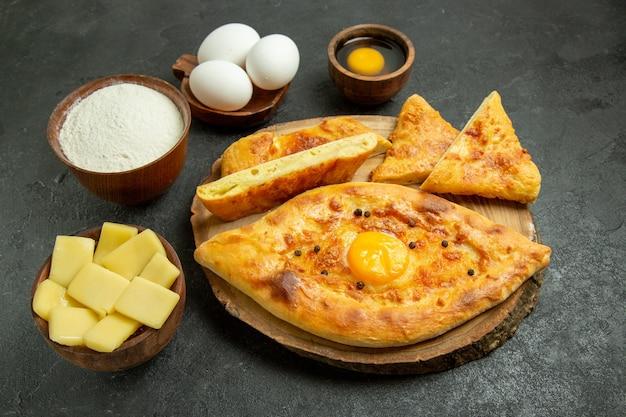 Vooraanzicht smakelijk eierbrood gebakken met kaas en bloem op de grijze ruimte