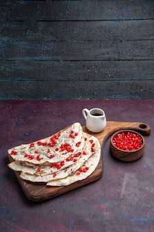 Vooraanzicht smakelijk vlees qutabs pitabroodjes met verse rode granaatappels op het donkerpaarse oppervlak voedsel vlees deeg pita