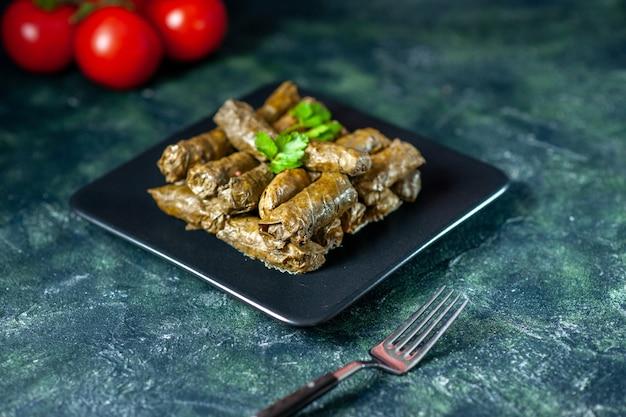 Vooraanzicht smakelijke blad dolma met tomaten op de donkere achtergrond calorie-olie diner voedselsalade schotel vlees restaurant maaltijd