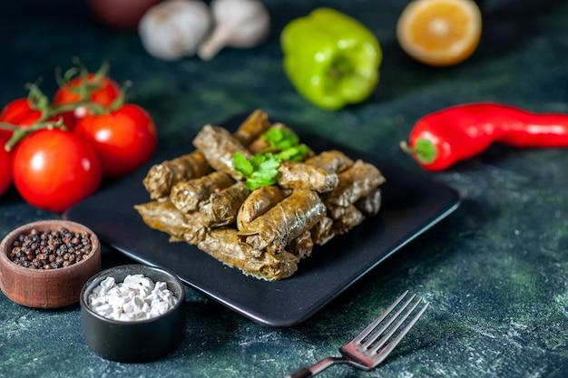 Vooraanzicht smakelijke blad dolma met tomaten op donkere bureau calorie-olie diner voedselsalade schotel vlees restaurant maaltijd
