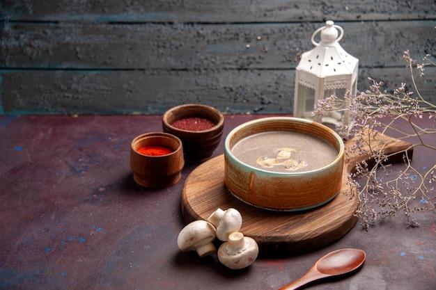 Vooraanzicht smakelijke champignonsoep met verschillende kruiden op de donkere ruimte