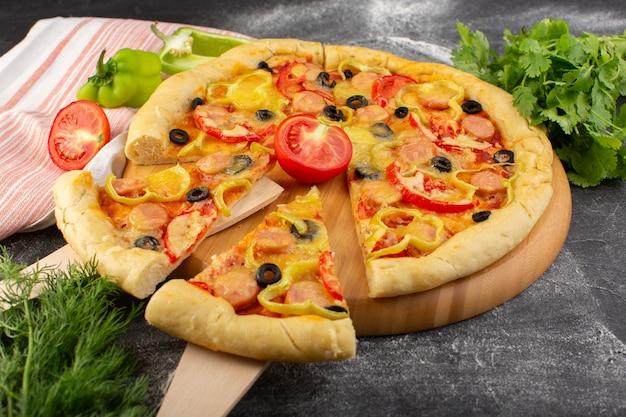 Vooraanzicht smakelijke cheesy pizza met rode tomaten, zwarte olijven, paprika en worstjes gesneden op grijs