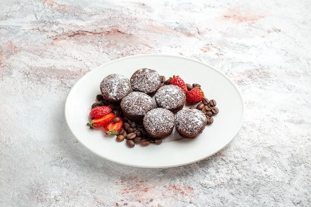 Vooraanzicht smakelijke chocoladecake met aardbeien en chocoladeschilfers op witte de cake van het oppervlaktebiscuit bak suiker zoete pasteikoekje