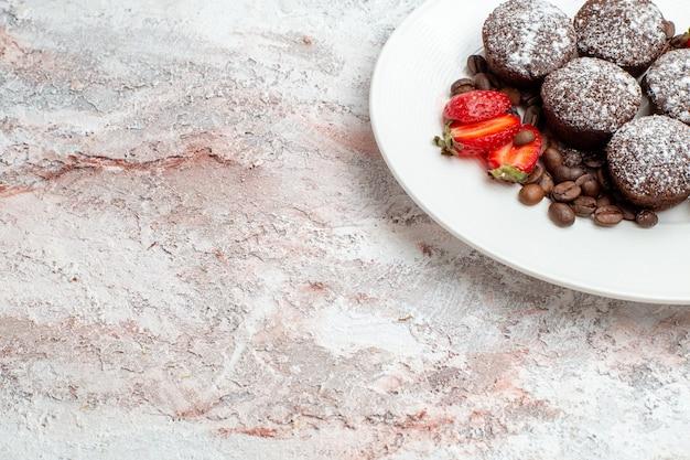 Vooraanzicht smakelijke chocoladetaart met aardbeien en chocoladeschilfers op lichte witte de cake van het oppervlaktebiscuit bak suiker zoete pastei koekjes