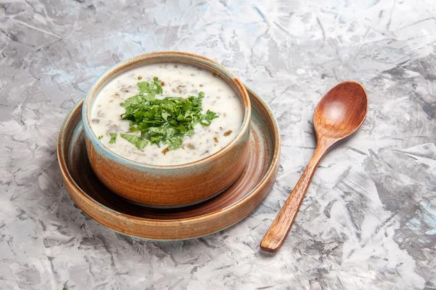 Vooraanzicht smakelijke dovga yoghurtsoep met greens op witte tafel zuivel melk soepschotel