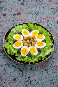 Vooraanzicht smakelijke eiersalade bestaat uit groene salade en olijven op lichte achtergrond