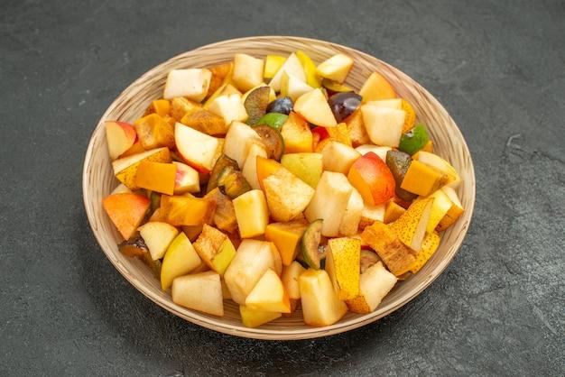 Vooraanzicht smakelijke fruitsalade bestaat uit vers fruit op de grijze tafel veel vers fruit