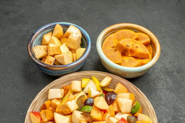 Vooraanzicht smakelijke fruitsalade met vers fruit op donkere tafel vers fruit veel