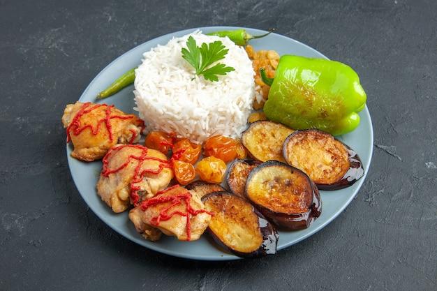 Vooraanzicht smakelijke gebakken aubergines met vlees gekookte rijst en rozijnen op donkere ondergrond
