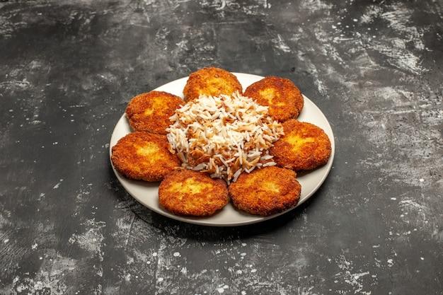 Vooraanzicht smakelijke gebakken schnitzels met gekookte rijst op donkere oppervlak foto vleesgerecht maaltijd