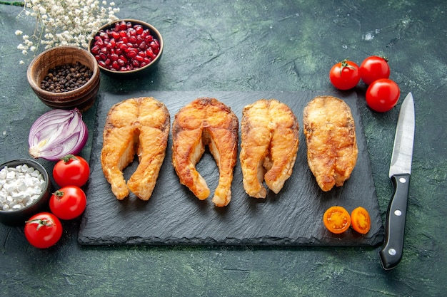 Vooraanzicht smakelijke gebakken vis met tomaten op donkere ondergrond koken schotel voedselsalade vlees gebraden zeemaaltijd zeevruchten peper